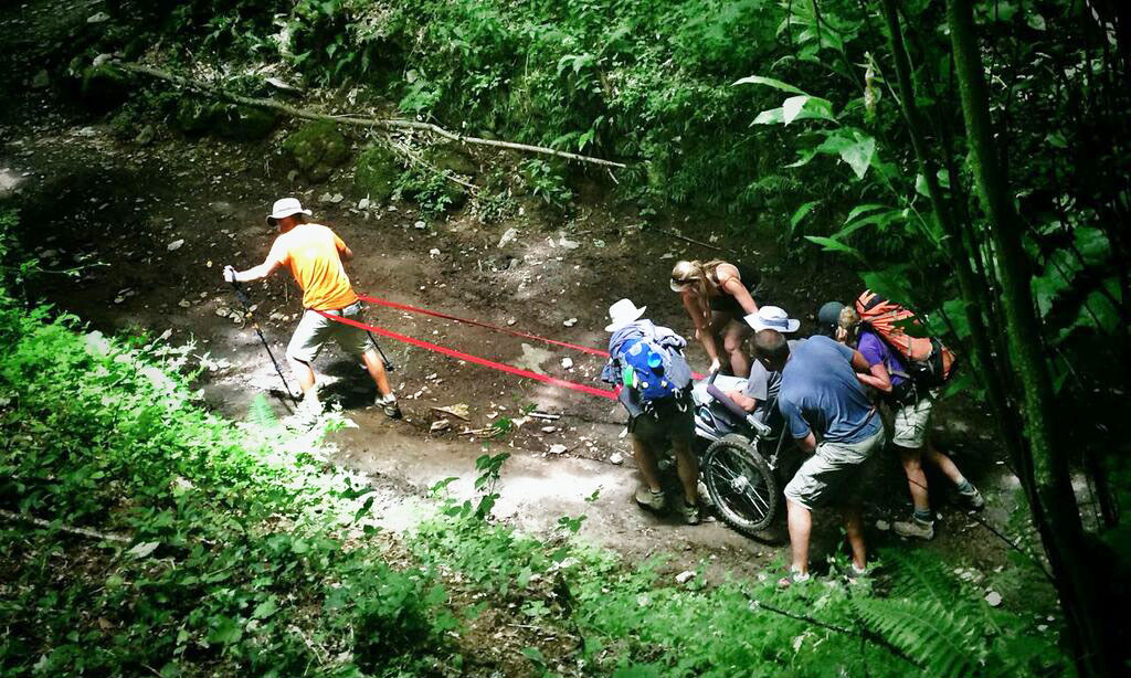 Justin being pulled through a creek bed in his custom wheelchair